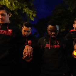 University of Utah football players hold hands and pray during a candlelight vigil remembering the life of slain student-athlete Aaron Lowe on Wednesday, Sept. 29, 2021 at University of Utah in Salt Lake City.