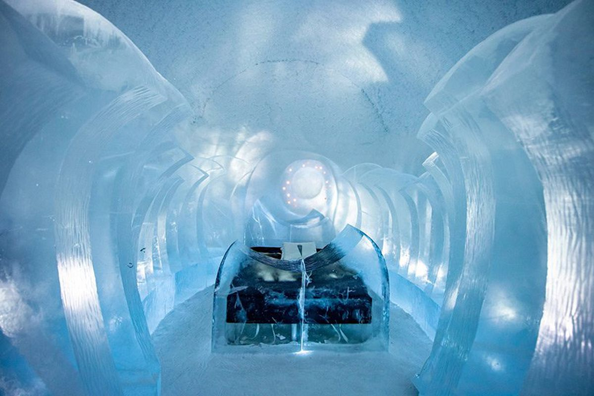 Large blocks of curving ice surround a bed.