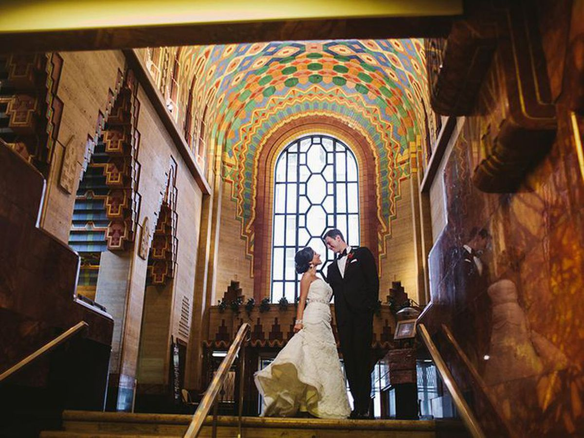 A woman and man embrace on the stairs in the Guardian Building in Detroit. The woman is wearing a wedding dress and the man is wearing a tuxedo. The ceiling is arched and decorated with an inlaid design.