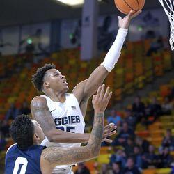 Utah State forward Dwayne Brown Jr. (25) takes a shot as Life Pacific forward Jonathan Cortez (0) defends during an NCAA basketball game, Saturday, Dec. 16, 2017, in Logan, Utah. (Eli Lucero/Herald Journal via AP)