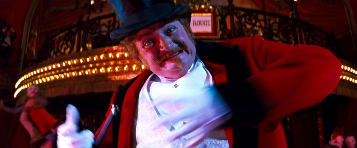 Jim Broadbent, dressed as a ringmaster, lunges at the screen in Moulin Rouge