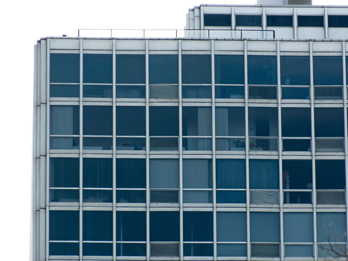 A top of a high-rise building with white steel and blue windows.