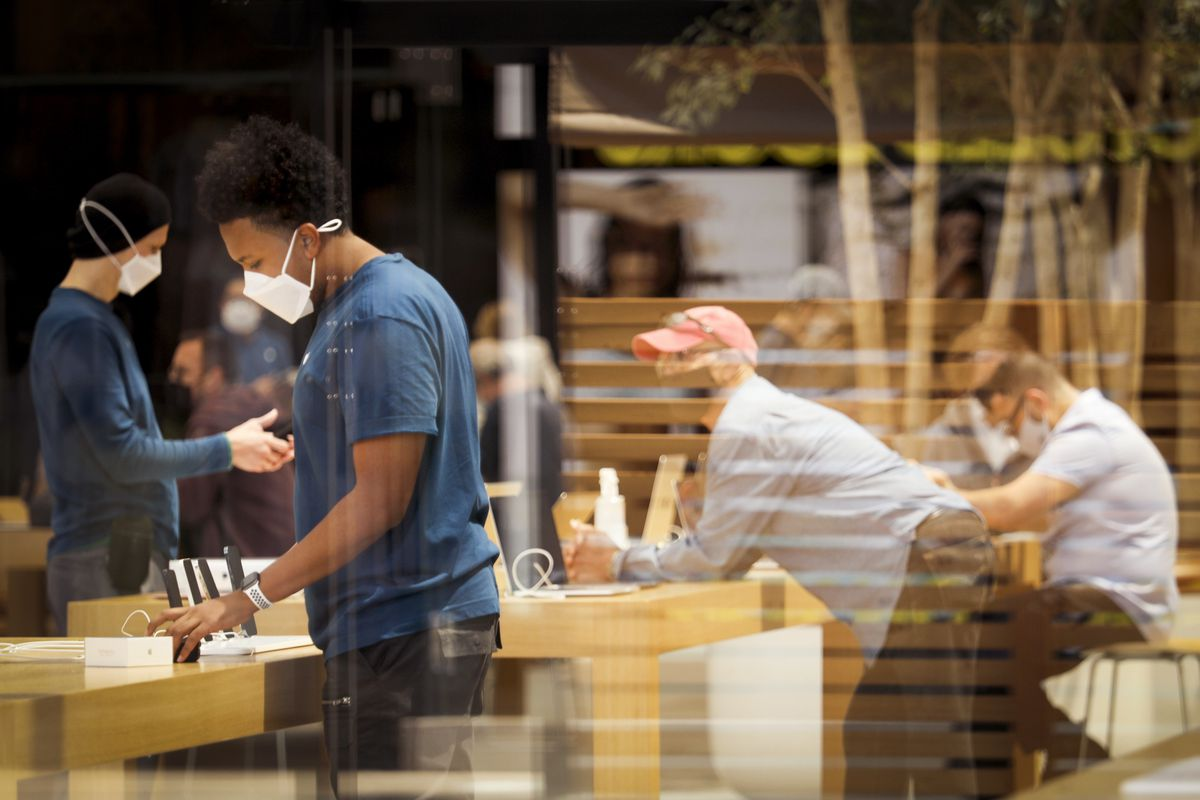 In a cafe, both servers and customers are fully masked and physically distanced, a day after the CDC relaxed its masking guidelines.
