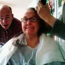 Peter Breinholt watches as Jane Breinholt has her hair shaved. A film was made to help her grandchildren laugh.