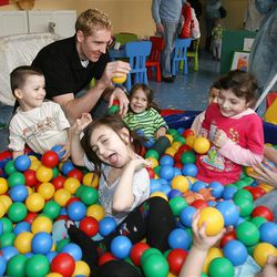 Travis Hansen plays with children in Russian orphanage. Travis and his wife LaRee co-founded the Little Heroes Foundation in 2007 in an effort to improve the lives of children worldwide.