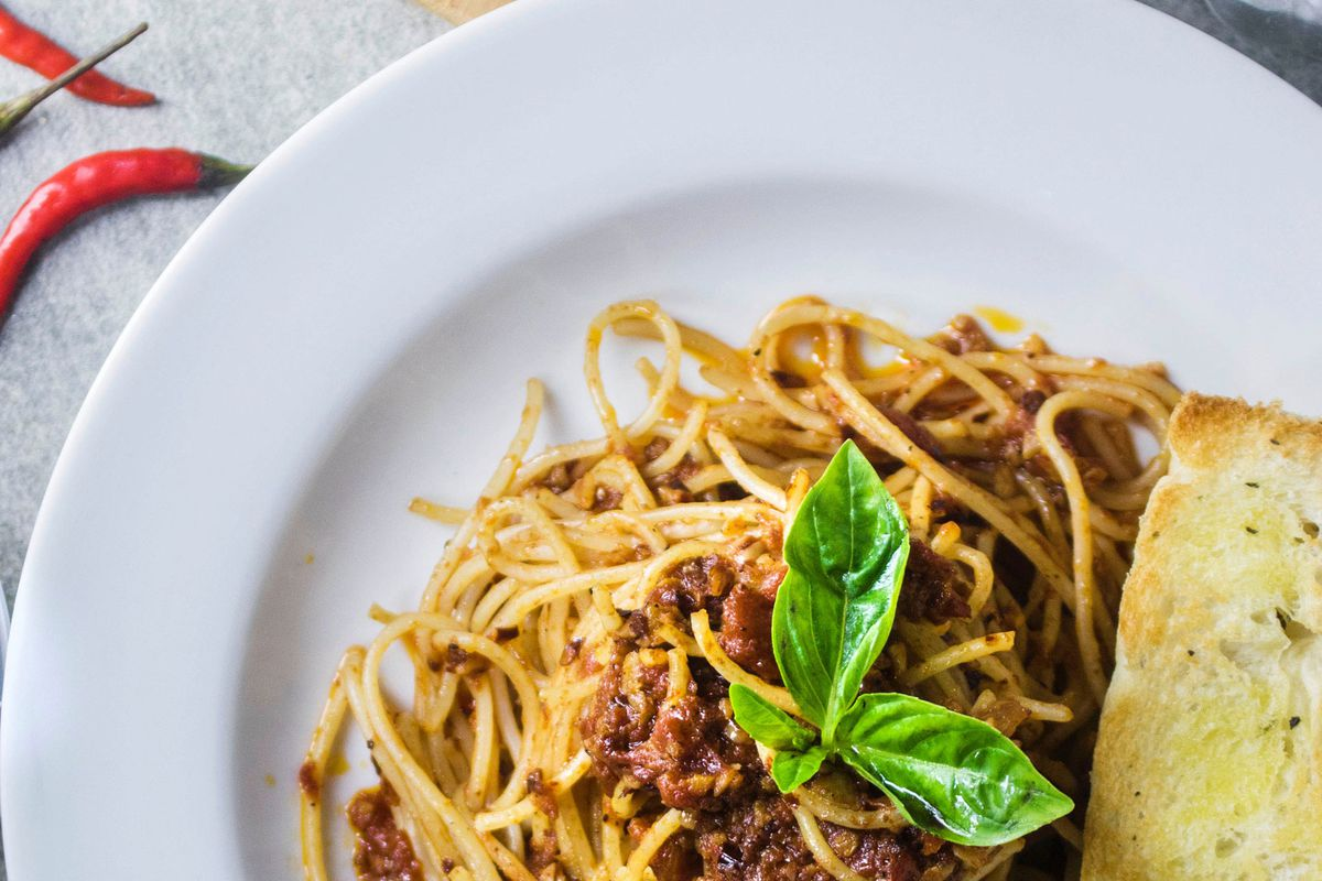 A plate of spaghetti up close, with basil on top.
