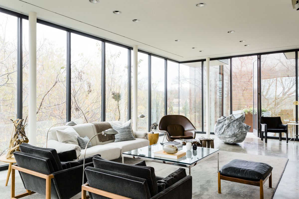 The living room is lined with windows. The furniture is modern and done in neutral colors.