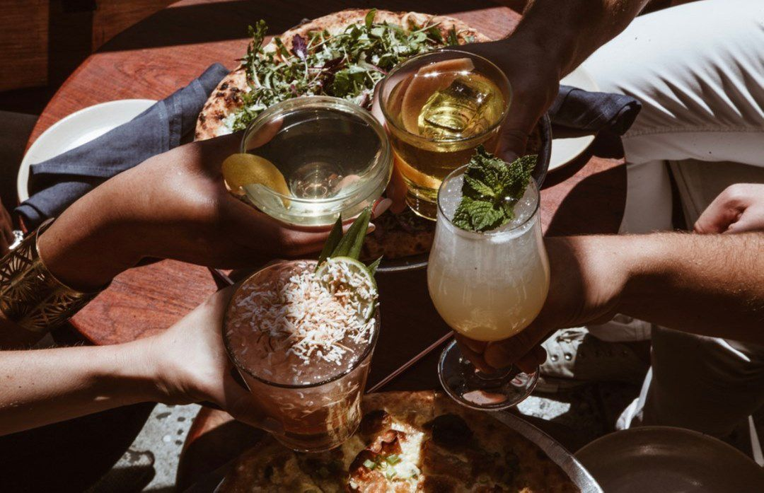 Group of friends toasting with different cocktail beverages