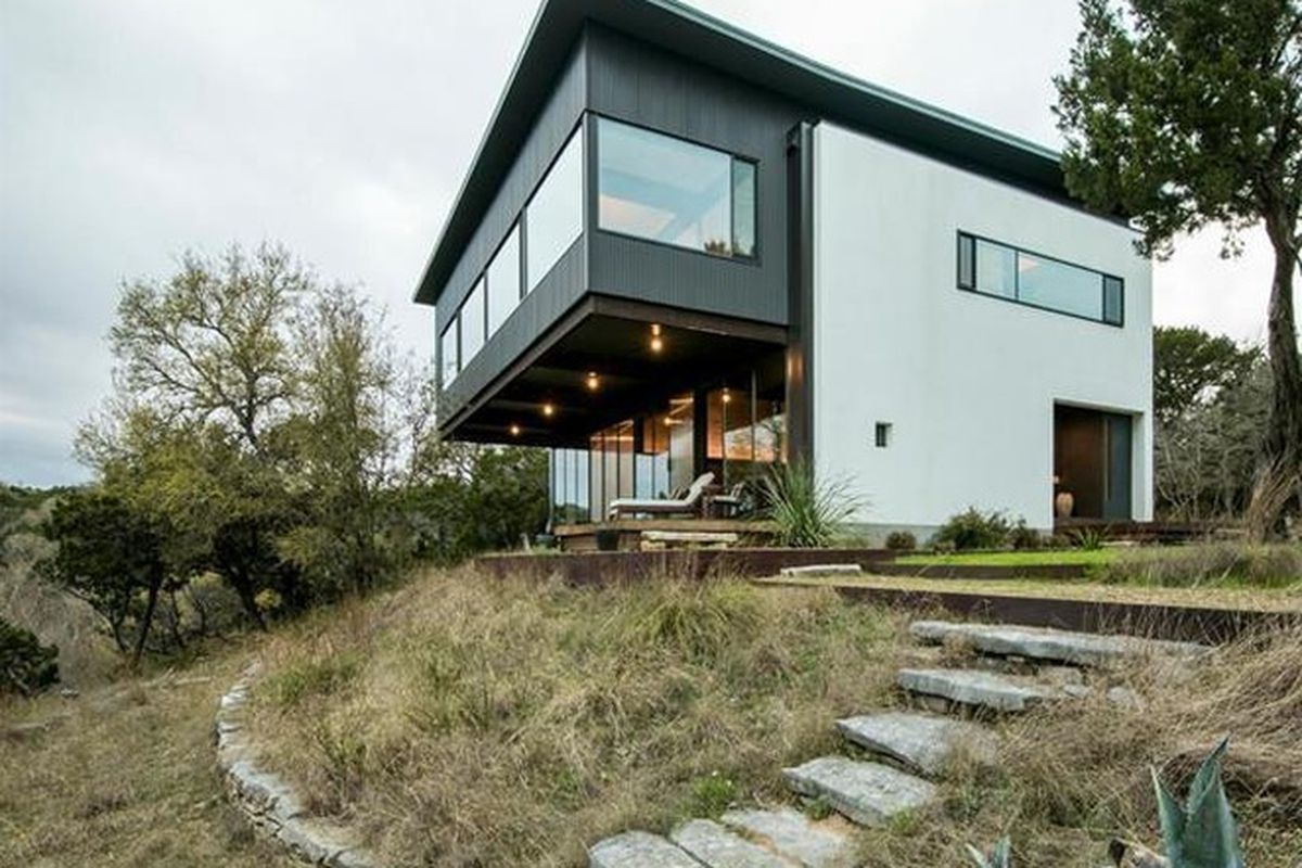 Two-story stucco house with cantilevered dark gray second story over porch