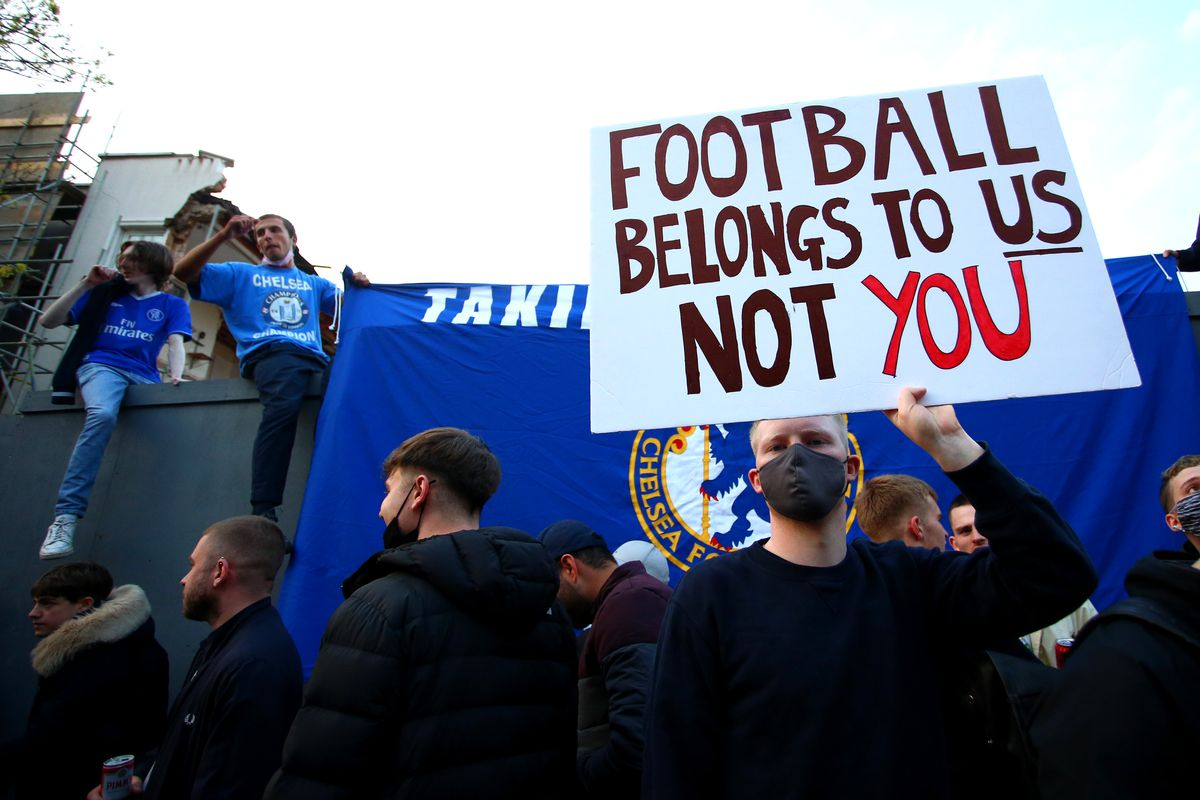 """A soccer fan holds a sign that reads """"Football belongs to us, not you."""""""