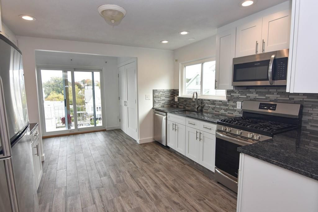 A large kitchen-dining room area leading to a sliding glass door that leads to a porch.