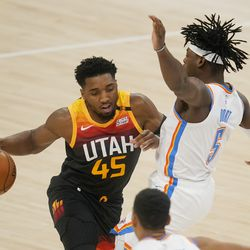 Utah Jazz guard Donovan Mitchell (45) drives against Oklahoma City Thunder guard Luguentz Dort (5) during the first half of an NBA basketball game in Oklahoma City, Monday, Dec. 28, 2020.