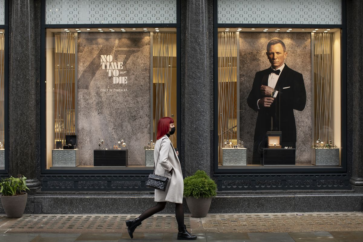 A woman walks past posters for a James Bond movie.