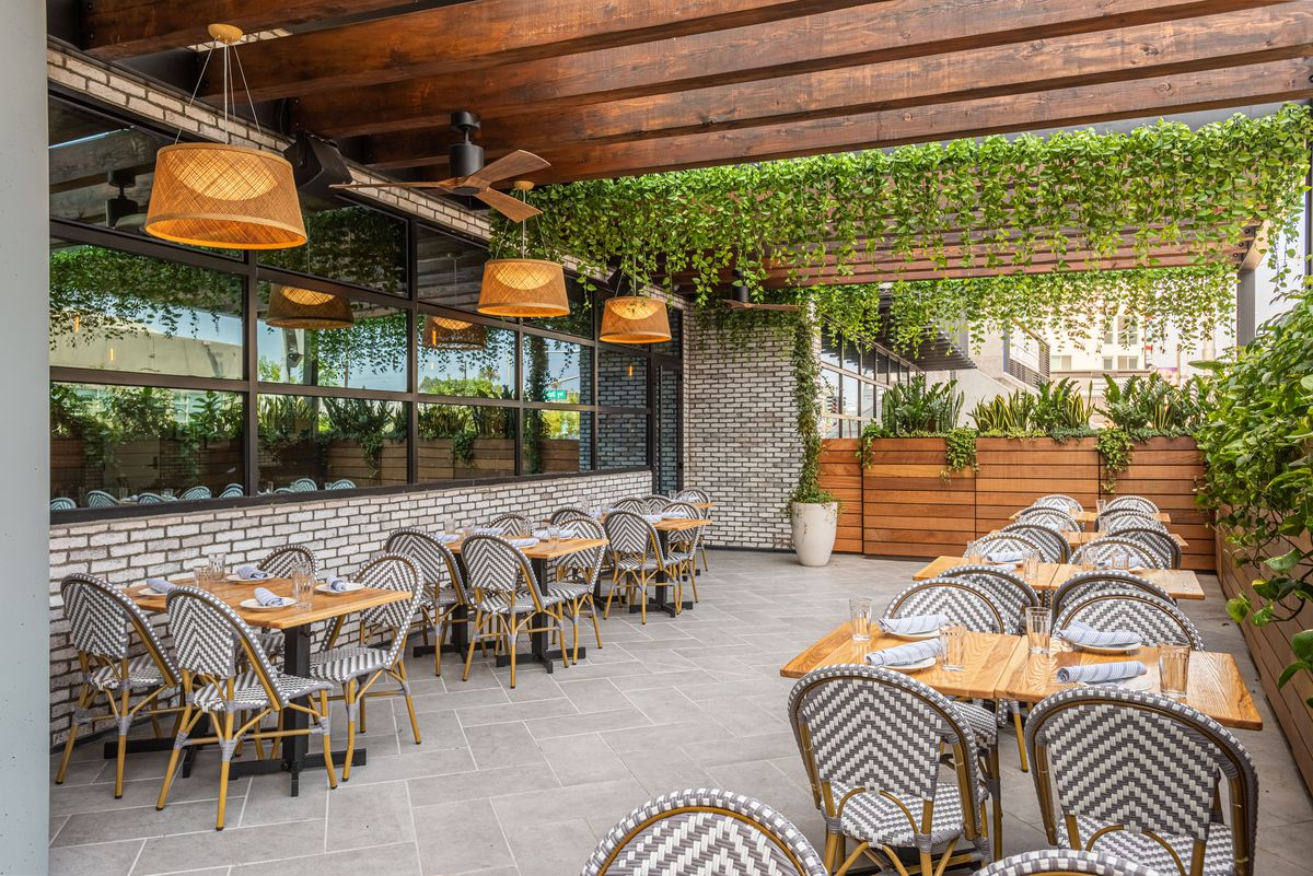 One side of a patio at a restaurant with cafe woven chairs and wooden tables.