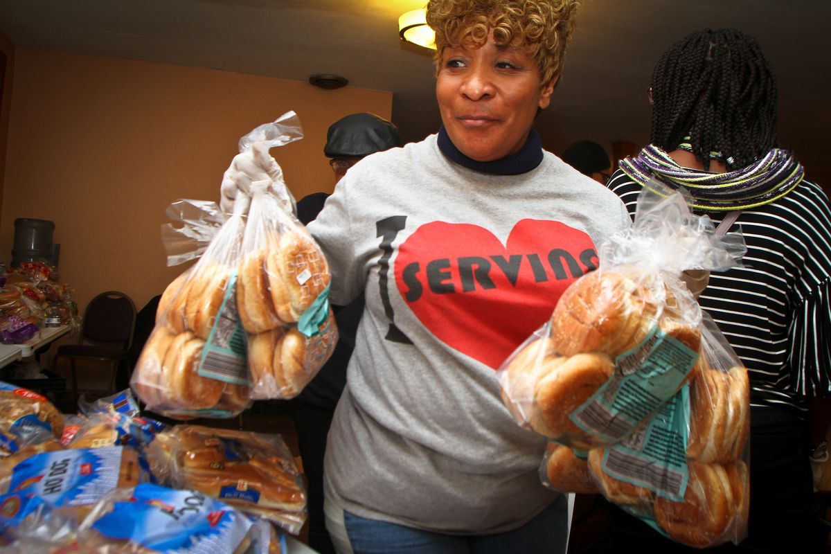 Toya Hallmon, food pantry volunteer at New Life Covenant Church, carries hamburger buns to the table as clients arrive.