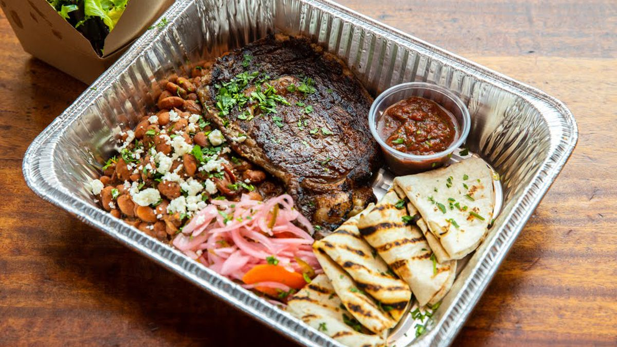 A steak, beans, tortillas, and pickled onions sit in a takeout container on a wooden table.