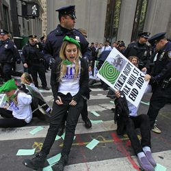 Police arrest members of a combined group of ACT UP and Occupy Wall Street activists who chained themselves and block traffic at Wall Street and Broadway, near the New York Stock Exchange, on Wednesday, April 25, 2012.  Police used chain cutters and wrestled protesters to the pavement in the middle of Broadway.
