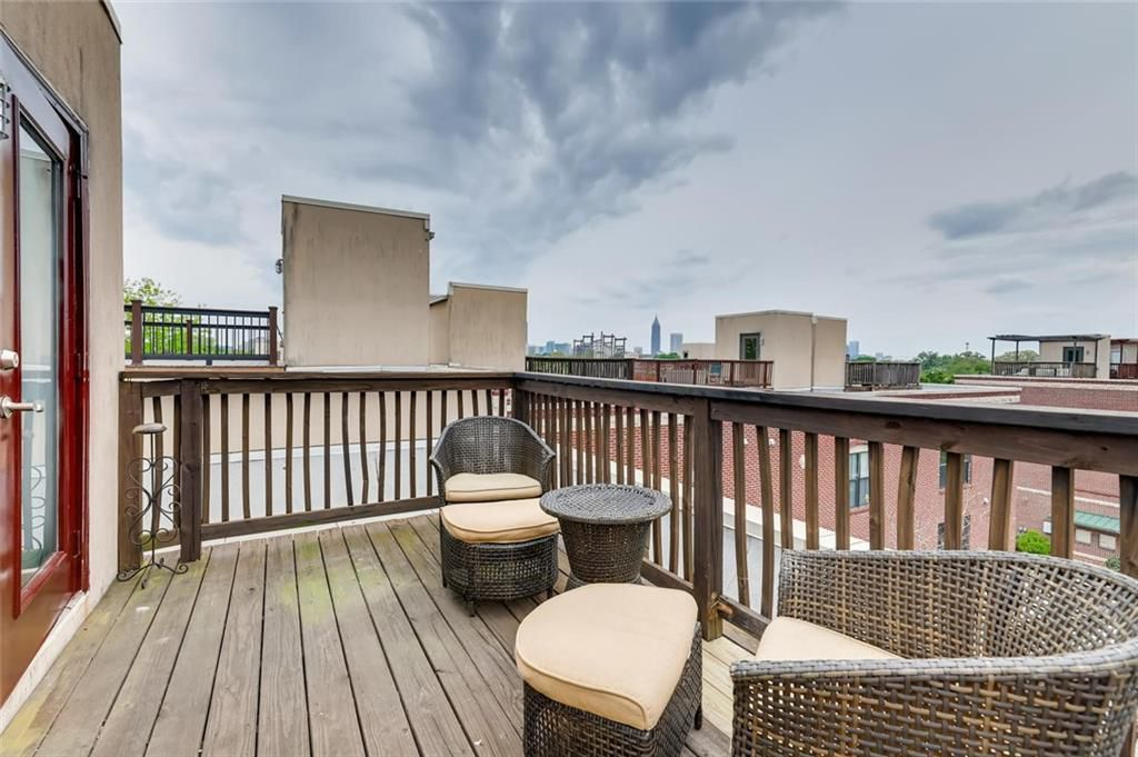 Rooftop deck with wicker chairs, ottomans, and table.