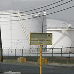 Gas storage tanks in Linden, N.J., are protected by chain-link fence.