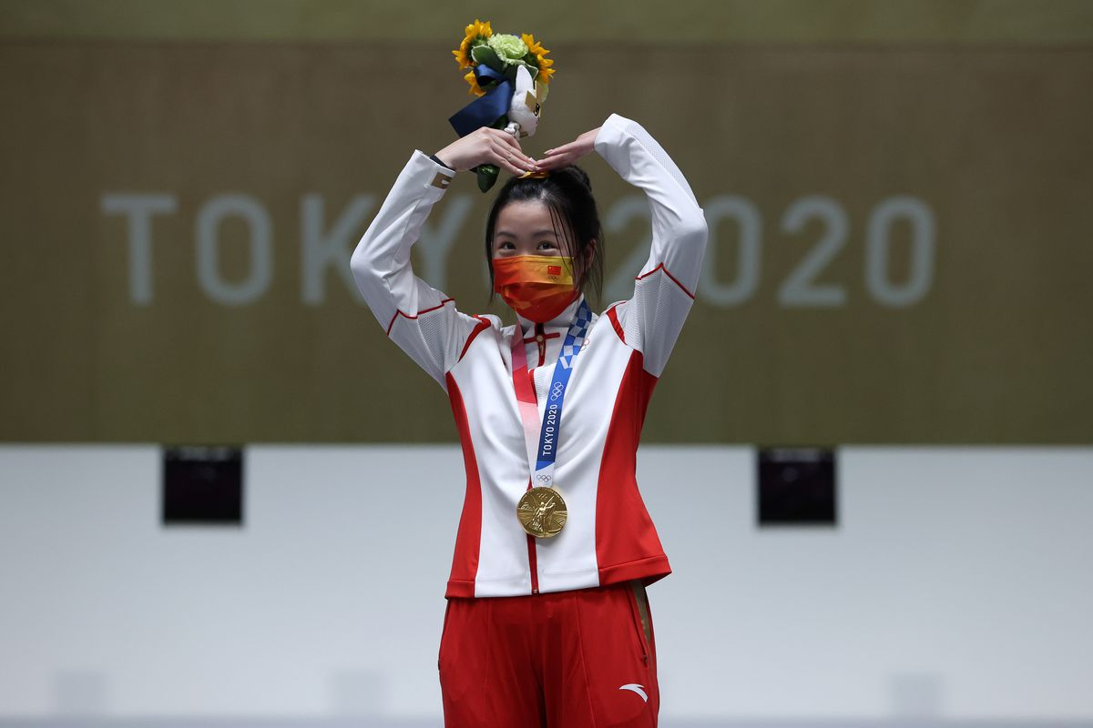 Gold Medalist Qian Yang of Team China poses on the podium during the medal ceremony for the 10m Air Rifle Women's event on day one of the Tokyo 2020 Olympic Games