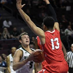 Utah Valley's Hayden Schenck (5) looks to pass the ball ad Seattle's Emmanuel Chibuogwu defends during the second half of an NCAA college basketball game in the first round of the Western Athletic Conference tournament Thursday, March 9, 2017, in Las Vegas. Utah Valley won 65-53.