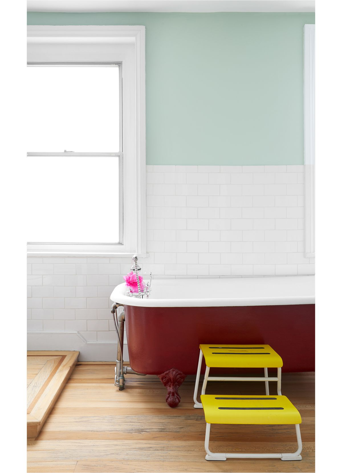 A bathroom. There is a bathtub which has a red exterior and a white interior. The walls of the bathroom are white tiles and light aqua blue. There is a yellow step stool in front of the bathtub. The floor is hardwood.