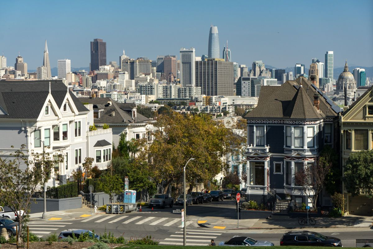 Painted Victorian houses in San Francisco, with the high-rise skyline behind them in the distance.