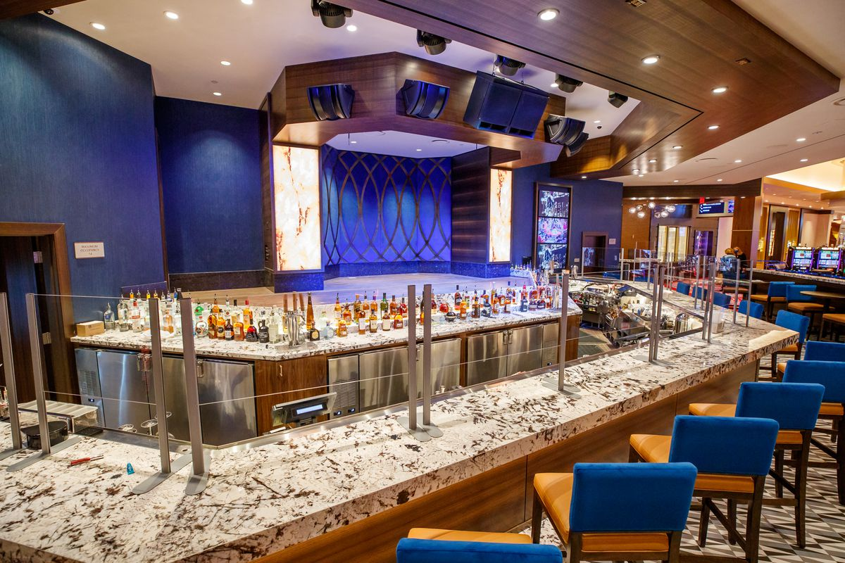 A restaurants marble bar with wire seats and liquor on the shelf.