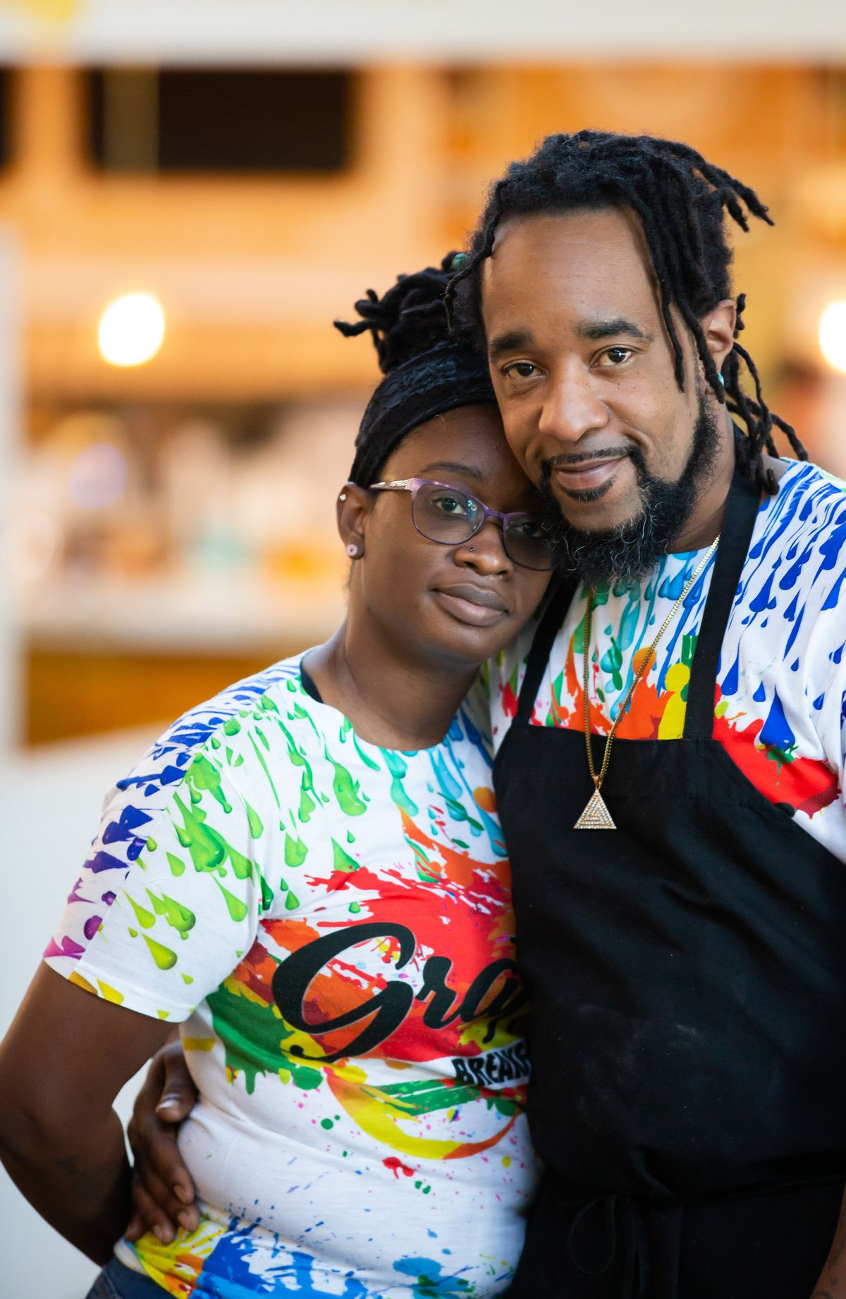 Owners Tonya Waller and chef Marcus James Waller wearing tie dye Graffiti Breakfast tees and Chef Waller wearing a black apron looking content as they hug one another