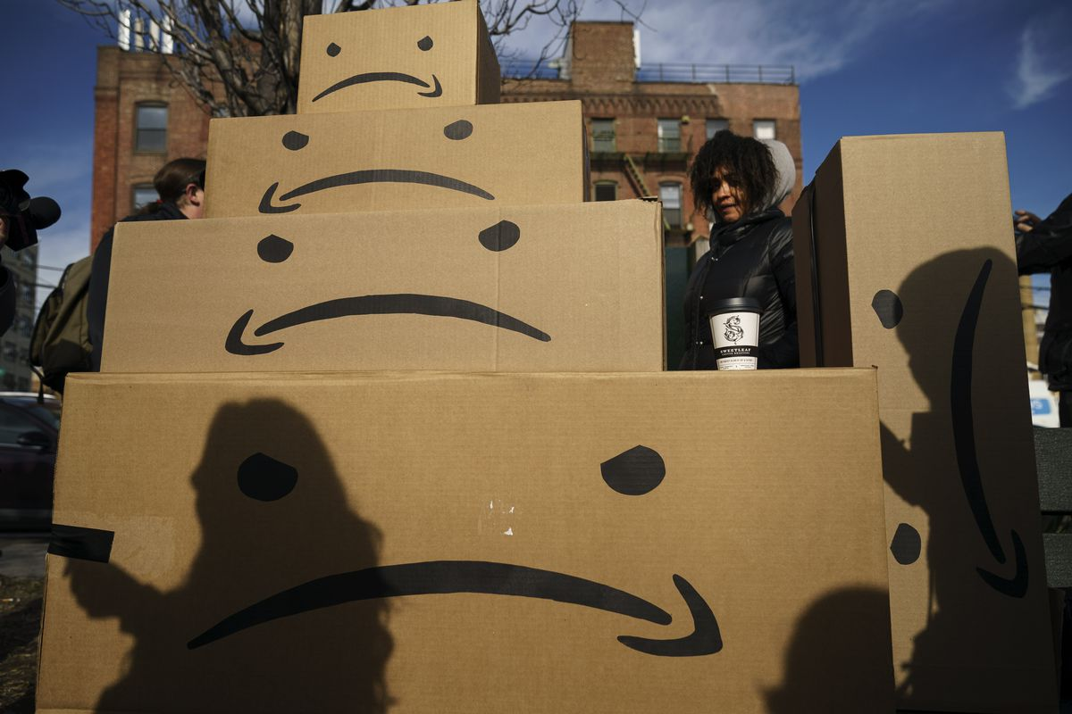 A stack of cardboard boxes with the Amazon smiling logo draw upside-down.