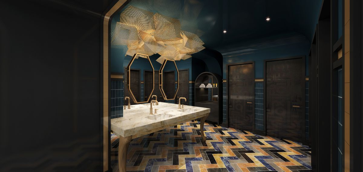 upscale public bathroom with colorful floor tiles, marble sinks, and gold light fixtures