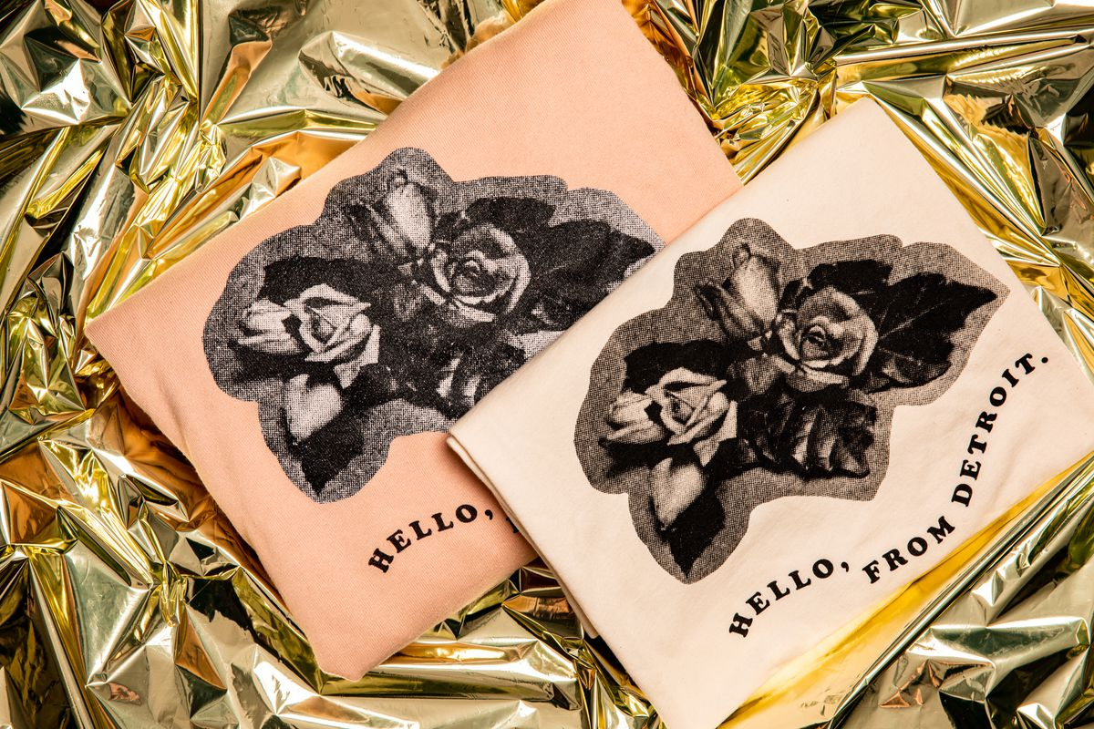 """A antique pink folded sweatshirt and a pale pink t-shirt reading """"Hello, From Detroit."""" with a decoupage-style design of black-and-white roses."""