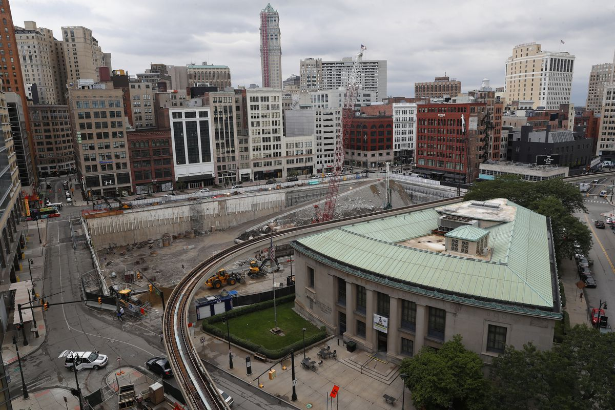 A high view of a rectangular construction site where a foundation is being built below ground. In the foreground is a triangular-shaped building with a copper roof. The background is filled with tall buildings.