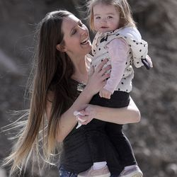 Whitney Beaslin holds daughter Charlotte outside of their apartment building in Sandy on Wednesday, April 1, 2020. Beaslin, a server and a single mom, is worried about getting evicted due to losing work from the COVID-19 pandemic.