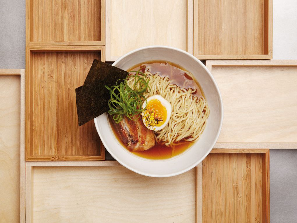 A bowl of ramen seen from above with noodles, egg, greens, slices of pork, and sheets of nori all sticking out of the bowl.