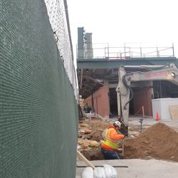 A hole being dug near the end of the left field bleachers