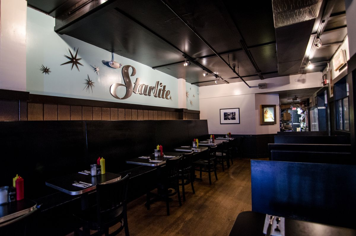 A vintage-looking dining room features wood paneling, light blue walls, and large silver letters spelling Starlite