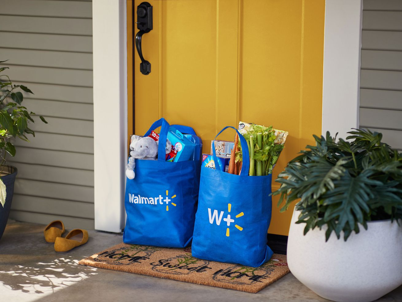 Two Walmart+ bags filled with groceries and other merchandise sit in front of the front door of a house.