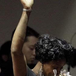 A woman raises her arm as she weeps during a memorial service at the Allen Temple Baptist Church Tuesday, April 3, 2012, in Oakland, Calif.Several hundred people gathered Tuesday night for a prayer vigil for the victims of Monday's shooting at Oikos University, a small Christian school in Oakland.
