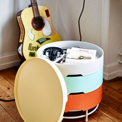A coffee table with stackable storage compartments.
