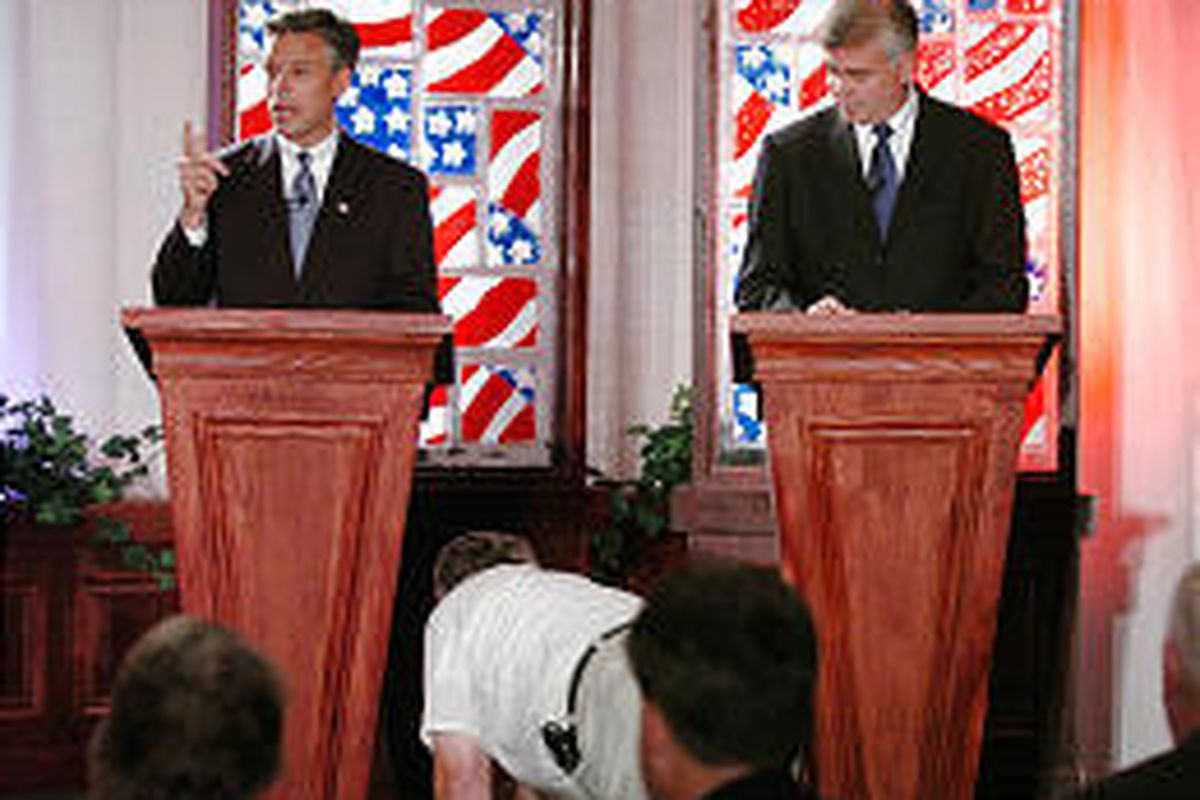 A worker tries to restore audio during the second debate between Jon Huntsman Jr. and Scott Matheson Jr., which was held in Provo Friday.
