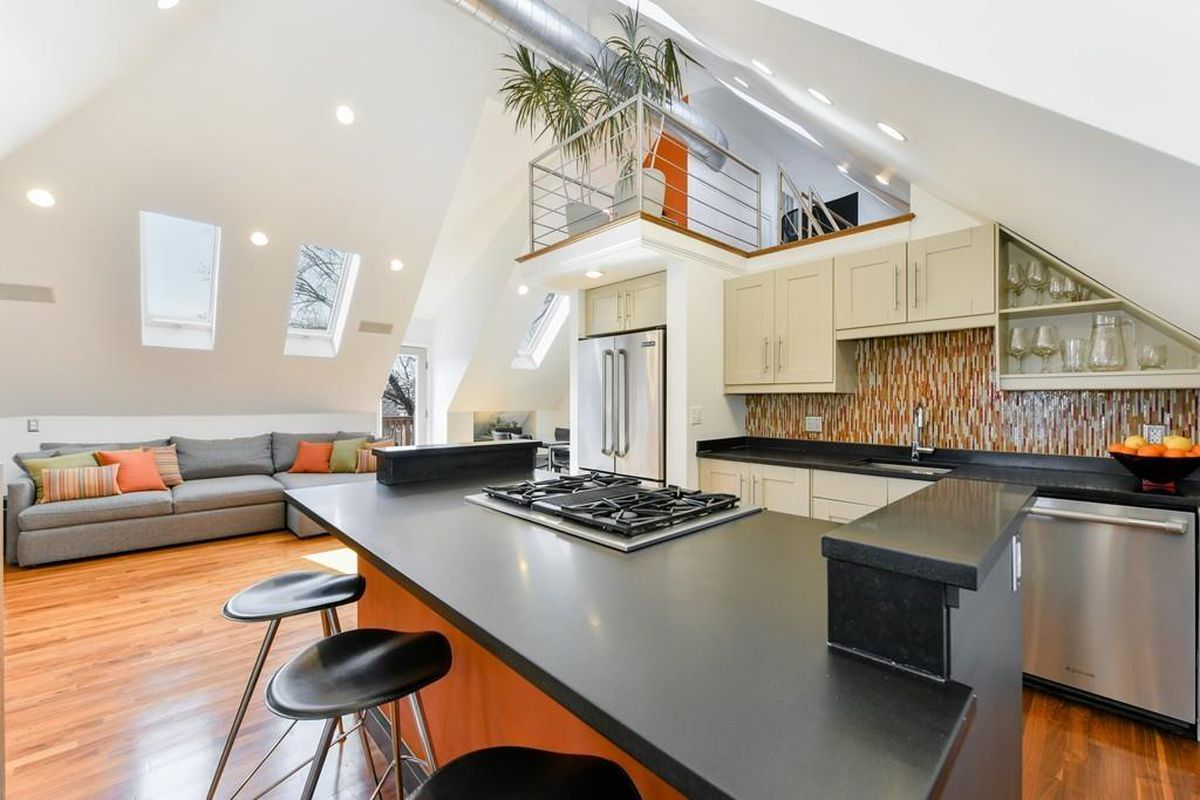 A cavernous open living room and kitchen, with an internal balcony jutting out.