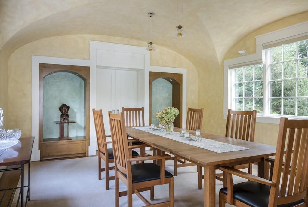 A dining room with a barrel roof, two shelves, and a long table with chairs around it.