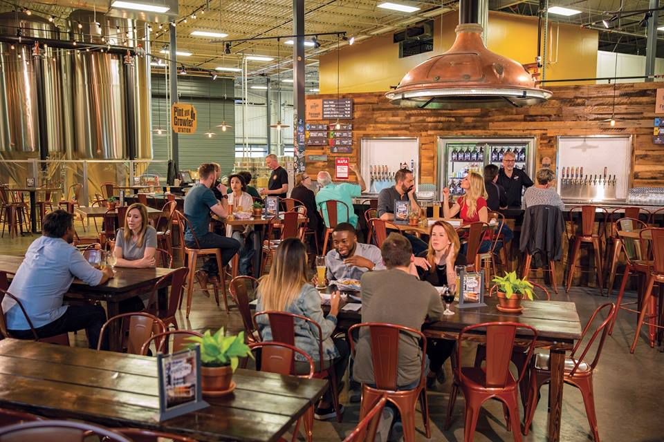 A warm, wood decorated taproom with a large copper light fixture, moderately filled with people