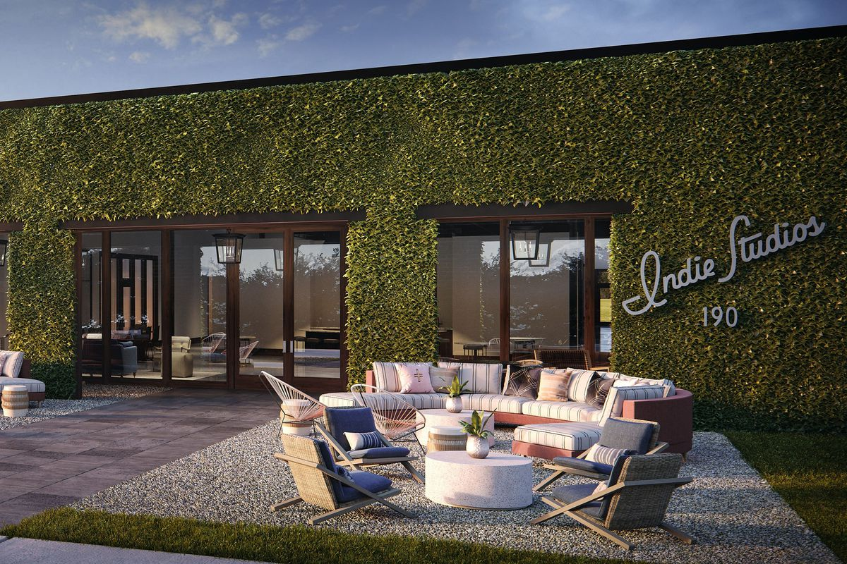 An outdoor patio space with green leafy wall and brick walls, in a rendering.