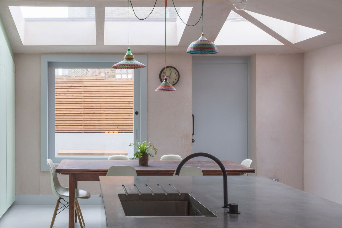 Interior shot of extension that comprises a kitchen and dining area with a large square window and skylights, a mint lacquered storage wall on one side and light pink plaster walls on the opposite side.