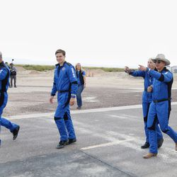 (Left to right) Mark Bezos, Oliver Daemen, Wally Funk and Jeff Bezos walk toward New Shepard's landing pad for a photo opp hours after returning from a quick trip to space.