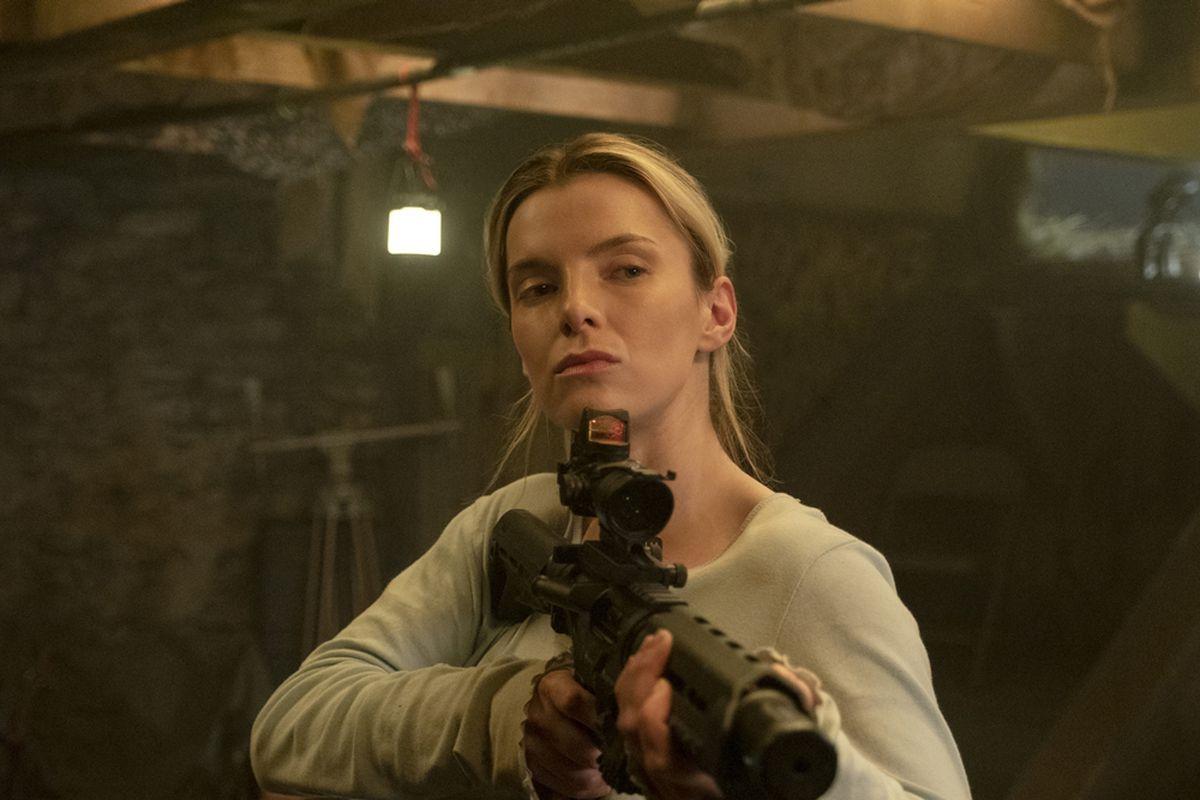 A woman holds a gun.