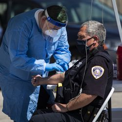 Norridge Police Department Officer Steven Deutscher gets his blood drawn for a coronavirus antibody test by a Simple Laboratories phlebotomist at the lab's drive-thru testing site in the parking lot of St. Rosalie Catholic Parish in Harwood Heights, Friday, May 1, 2020.