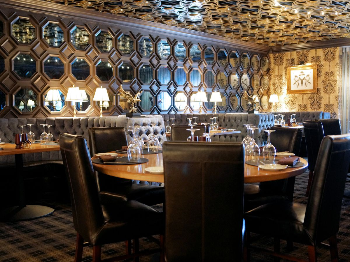 Restaurant interior featuring mirrored walls and film reels on ceiling